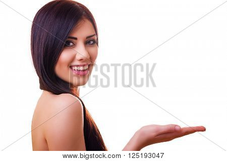 Beautiful young brunette smiling and holding something on a palm - isolated on white with copy-space