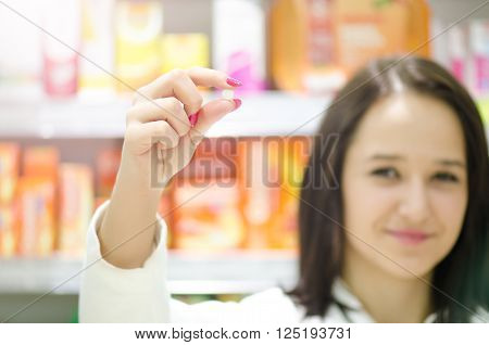 Pharmacist chemist woman show a pill. Pharmacy drugstore is background. Pretty, young laborant.