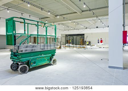 Scissor lift platform is inside of new big hall in building process. Shopping center