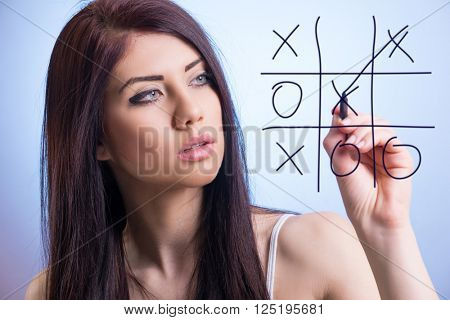 Beautiful young brunette playing and winning in a tic-tac-toe game