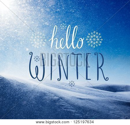 Photo of snowstorm in sunny day with Hello Winter lettering. Winter holidays card