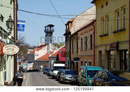 Wieliczka, Poland - April 04, 2016: Sikorskiego street. Townhouses and people walking down the street. In the background historic salt mine - shaft