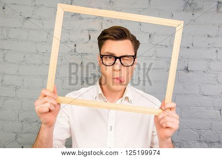 Handsome Man In Glassesd Showing Tongue And Winking With Frame