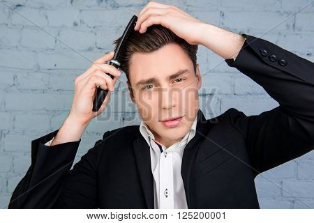 Portrait Of Young Pretty Man Combing His Hair On The Background Of Wall