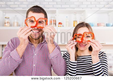 Comic Couple In Love Holding Slices Of Pepper Near Eyes And Showing Tongue