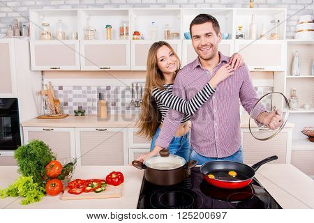 Happy Young Man And Woman Hugging And Cooking  In The Kitchen