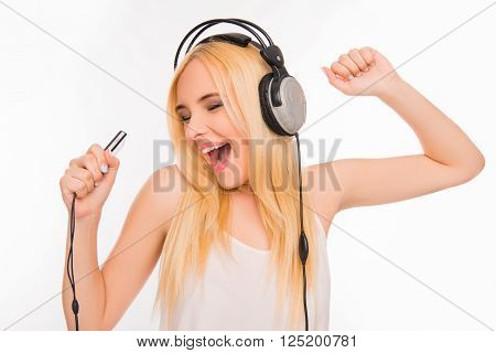 Cheerful Pretty Girl Listening Music In Headphones And Singing