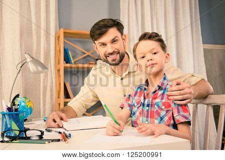Portrait of happy young father helping his son with homework