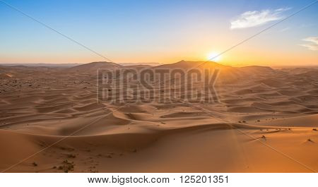 Lonely sand dunes under dramatic evening sunset sky at drought desert landscape