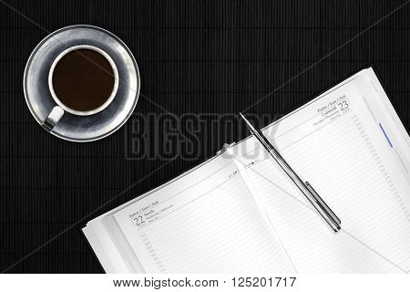 Calendar and silver pen on black desk with coffee in metal mug