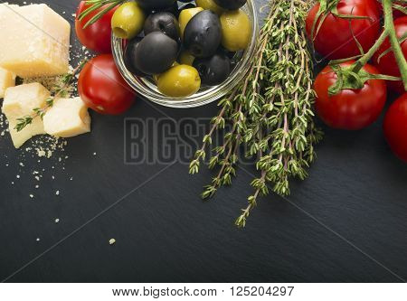 Cheese with fresh herbs, black and green olives, cherry tomatoes,  on a black board.