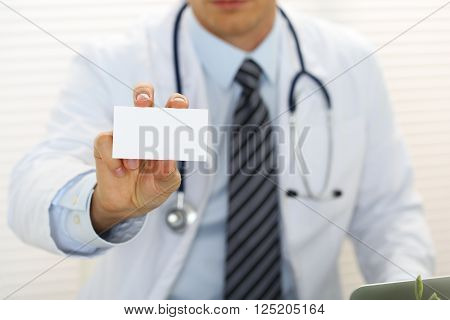 Male Physician Hand Holding And Giving White Blank Calling Card