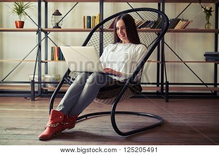 Girl sitting in a chair working on laptop, on the background of bookshelves