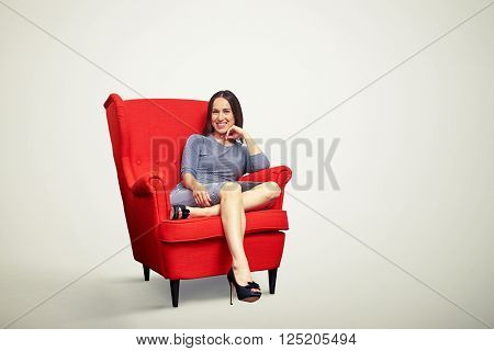 Young pretty girl is smiling and holding her hand near chin while sitting in soft red chair