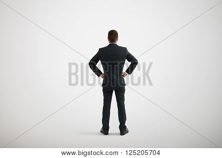 Back view of standing man in a formal clothes with his hands akimbo