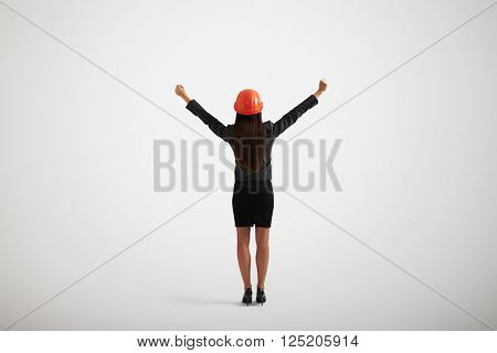 Back view of woman in formal wear and construction helmet rising her hands upwards and outwards