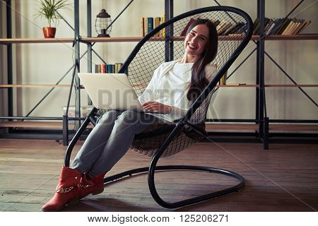 Girl sitting in a chair and working on laptop, on the background of bookshelves