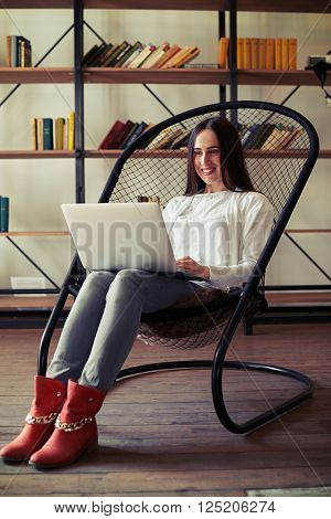 Girl in red shoes and blue jeans working on her laptop while sitting on a comfortable chair, on the background of bookshelves