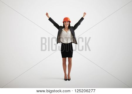 Happy smiling woman in formal wear and hard hat rising her hands upwards and outwards