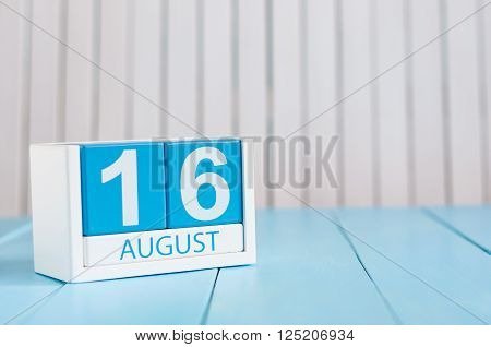August 16th. Image of august 16 wooden color calendar on blue background. Summer day. Empty space for text.