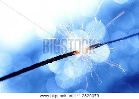 sparkler on blue bokeh background