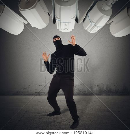 Cameras pointed at a hooded fearful man