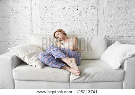 young beautiful red hair woman holding with her hands a hurting belly suffering stomach cramp and period pain sitting on home couch in sad face expression in female menstruation concept