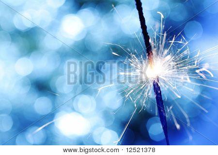 Sparkler auf blau Bokeh Hintergrund