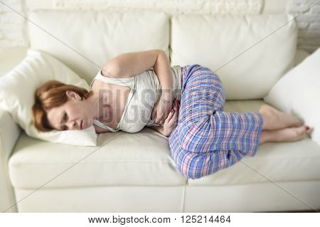 young beautiful red hair woman with hands on her belly or tummy suffering stomach cramp and period pain lying on home couch in painful face expression female menstruation concept