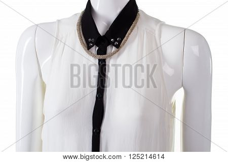 Blouse with necklace on mannequin. Woman's silver necklace and blouse. Rhinestones on blouse collar. Evening garment with necklace.