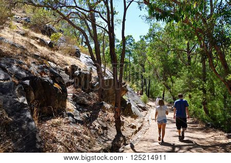 SERPENTINE,WA,AUSTRALIA-JANUARY 30,2014: People hiking through the natural granite rock wall landscape with green trees in Serpentine National Park in Serpentine, Western Australia.