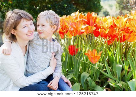 happy smiling mother and her loving son hugging and spending time together in the beautiful blooming park at spring time mother's day concept