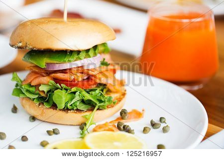 delicious salmon bagel served for breakfast with carrot orange juice, healthy eating concept