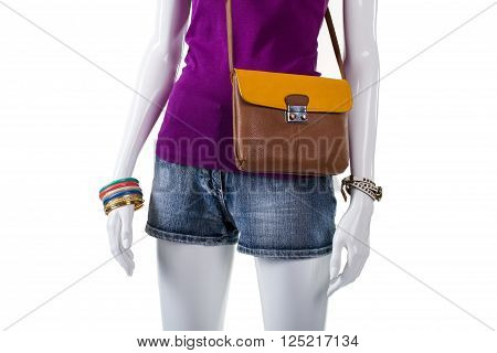 Purple top with bicolor bag. Purse with strap on mannequin. Woman's trendy handbag and shorts. Stylish clothing for modern youth.