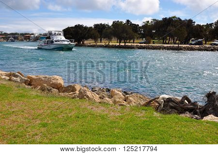 MANDURAH,WA,AUSTRALIA-MARCH 7,2014: Yacht with people boating through the glistening canals running through a green manicured treed setting under a blue sky with clouds in Mandurah, Western Australia.