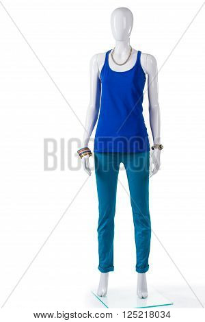 Turquoise pants with blue top. Female mannequin wearing turquoise pants. Bright-colored spring pants. New cotton trousers on sale.