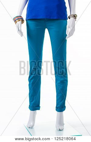 Woman's plain turquoise pants. Mannequin wearing folded turquoise trousers. Fashionable pants for spring. New clothes from spring collection.