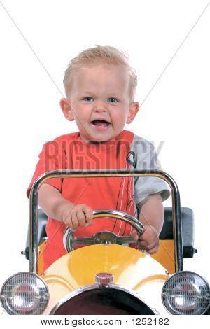 Blond Boy Driving A Toy Car