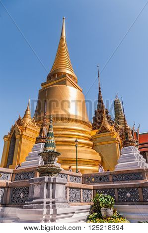 Large Golden Temple Spire against a dark blue sky at the Grand Palace, Bangkok, Thailand.