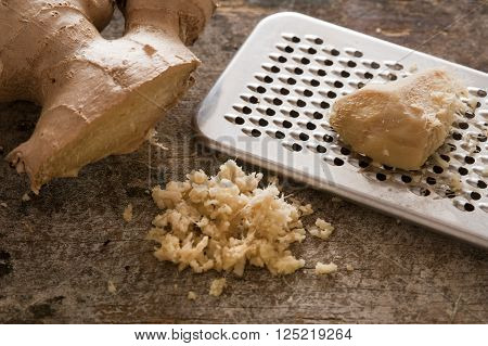 One stainless steel grater next to whole ginger root and shreds on a rustic table