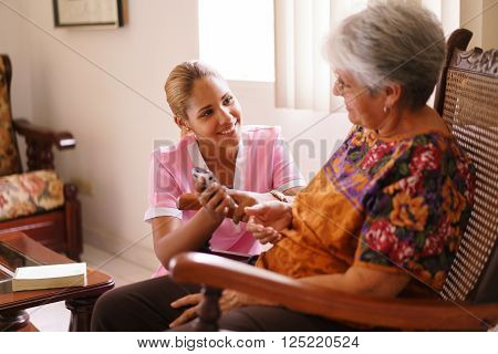 Old people in geriatric hospice: elderly lady having eyesight problems viewing the screen of mobile phone. A nurse helps the senior woman dialing a number on the tiny keyboard