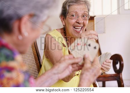 Old people in geriatric hospice: group of senior women playing cards and having fun together. An aged lady wins the game and shows a card to her rival