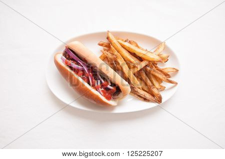 bratwurst sausage on a bun with french fries ketchup and onions