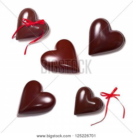Love concept: chocolate hearts and red ribbons on a white background