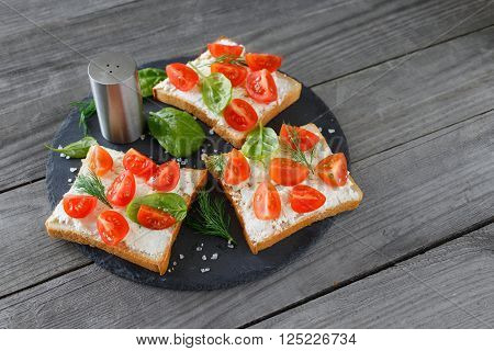 Tomato and cheese bruschetta on a ceramic cutting board top view with copy space. Healthy food