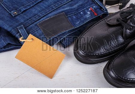 Set of men's clothing shoes jeans and a belt with blank tag on white wooden background top view