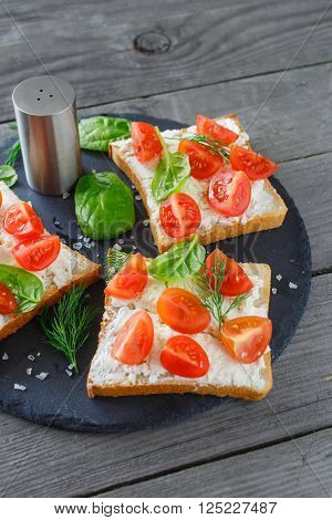 Tomato and cheese bruschetta on a ceramic cutting board, closeup. Delicious and healthy food