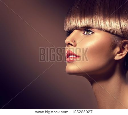 Beauty Woman with beautiful make up and healthy smooth brown hair, fringe hairstyle. Attractive Fashion Model with Long and Healthy Brown Hair. Beauty Brunette Girl on dark background