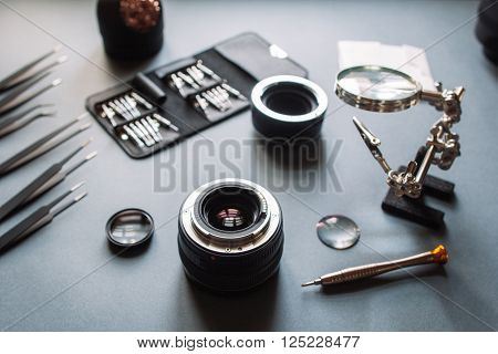 Precision optical dslr lens service, adjustment and alignment. Camera lens repair set in photo engineer workshop. Maintenance support of photographic 50 1.4 photo camera lens.