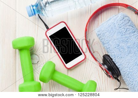 Fitness and diet concept. Dumbbells, water bottle, smartphone and towel. Top view with copy space